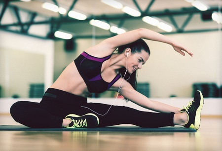 32337262 - fitness, sport, training, gym and lifestyle concept - stretching young woman with earphones in the gym