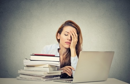 35882708 - too much work tired sleepy young woman sitting at her desk with books in front of laptop computer isolated grey wall office background. busy schedule in college, workplace, sleep deprivation concept