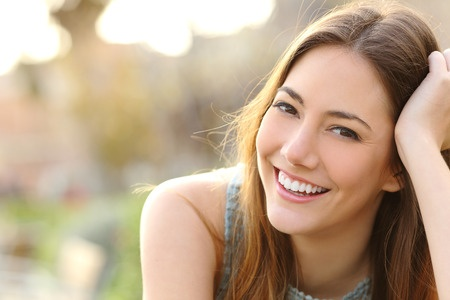 40317248 - woman smiling with perfect smile and white teeth in a park and looking at camera